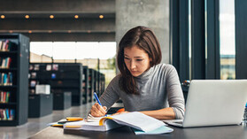 Female student taking notes from a book at library. Young asian woman sitting at table doing assignments in college library. People, school, acoustics.