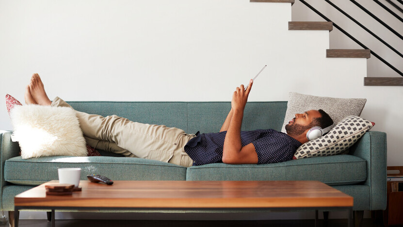 Man Lying On Sofa At Home Wearing Headphones; Shutterstock ID 1125901364;  Used for Sustainability Report 2018. 20s; at home; entertainment; headphones; horizontal; indoors; lounge; lying; male; man; online; people; person; relaxed; relaxing; sofa; tablet